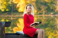 Härlig kvinna med boken på nedgångnaturbakgrund Royaltyfria Bilder