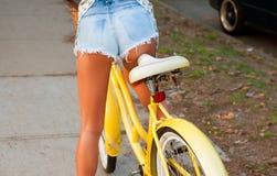 Härlig kvinna med cykeln på gatan royaltyfri bild