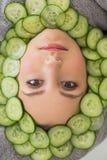 Härlig kvinna med den ansikts- maskeringen av gurkaskivor på framsida Royaltyfria Foton