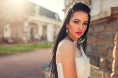 Härlig kvinna med den bärande vita bröllopsklänningen för långt hår utomhus Skönhetmodemodell med smycken och makeup royaltyfria bilder