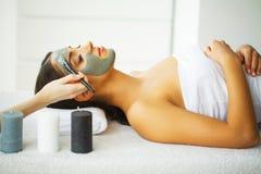 Härlig kvinna med den kosmetiska maskeringen på framsida Flickan får behandling arkivfoto