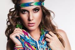 Härlig kvinna med den mång- halsbandet och örhängen Royaltyfri Foto
