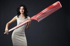 Härlig kvinna med den massiva hårkammen i henne händer. Arkivfoton