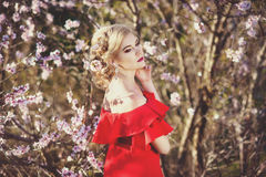 Härlig kvinna med den perfekta sunda hudståenden Kvinnlig flicka för mode som trycker på upp hennes framsida i blommande trädgård Royaltyfria Bilder