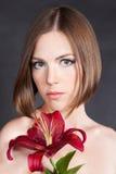 Härlig kvinna med den röda blomman royaltyfria foton