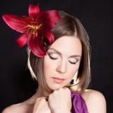 Härlig kvinna med den röda blomman arkivfoto