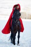 Härlig kvinna med den röda kappan med den utomhus- hästen royaltyfria bilder