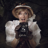 Härlig kvinna med den retro kameran i djungeln Arkivfoto
