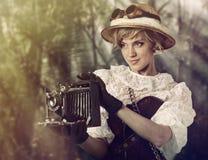 Härlig kvinna med den retro kameran i djungeln Arkivbild