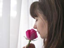 Härlig kvinna med den rosa rosen nära fönstret arkivfoto