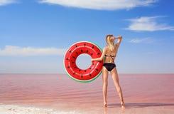 Härlig kvinna med den uppblåsbara cirkeln som poserar nära rosa färger royaltyfri foto