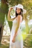 Härlig kvinna med den vita solhatten Fotografering för Bildbyråer