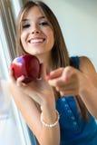 Härlig kvinna med det hemmastadda röda äpplet Arkivbild