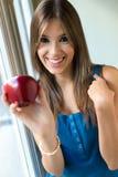 Härlig kvinna med det hemmastadda röda äpplet Arkivfoton
