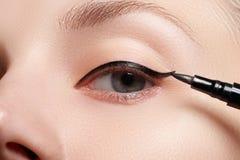 Härlig kvinna med det ljusa sminkögat med sexig svart eyelinermakeup Modepilform Chic aftonsmink Makeupskönhetintelligens Royaltyfri Foto