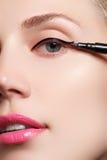 Härlig kvinna med det ljusa sminkögat med sexig svart eyelinermakeup Modepilform Chic aftonsmink Makeupskönhetintelligens Royaltyfria Bilder