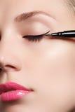 Härlig kvinna med det ljusa sminkögat med sexig svart eyelinermakeup Modepilform Chic aftonsmink Makeupskönhetintelligens Arkivbild
