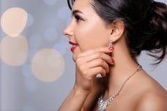 Härlig kvinna med eleganta smycken på suddig bakgrund, closeup royaltyfria bilder