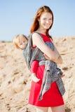 Härlig kvinna med en behandla som ett barn i en rem behandla som ett barn momen Moder och arkivbilder
