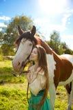 Härlig kvinna med en häst i fältet Flicka på Arkivfoto