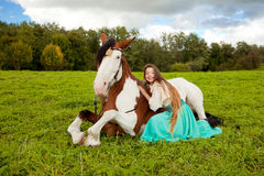 Härlig kvinna med en häst i fältet Flicka på Arkivbilder