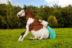 Härlig kvinna med en häst i fältet Flicka på Arkivfoton
