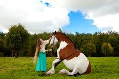 Härlig kvinna med en häst i fältet Flicka på Royaltyfria Bilder