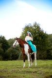 Härlig kvinna med en häst i fältet Flicka på Arkivbild