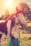 Härlig kvinna med en häst i fältet Flicka på en lantgård med a Arkivbild
