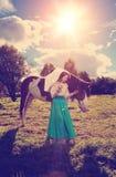 Härlig kvinna med en häst i fältet Flicka på en lantgård med a Fotografering för Bildbyråer