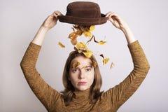 Härlig kvinna med en hatt som är full av höstsidor arkivfoto