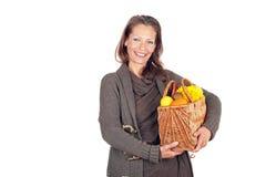 Härlig kvinna med en korg som är full av frukter och blommor Arkivfoton