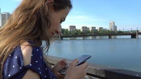 Härlig kvinna med en smartphone nära floden lager videofilmer