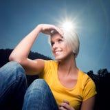 Härlig kvinna med en sunburst över hennes huvud Royaltyfri Foto