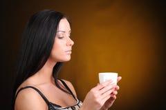 Härlig kvinna med ett aromatiskt kaffe i händer Arkivfoto