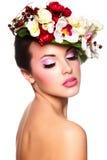 Härlig kvinna med färgrika blommor på huvudet Fotografering för Bildbyråer