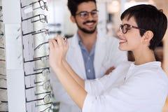 Härlig kvinna med försökande glasögon för optiker royaltyfria bilder