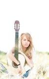 Härlig kvinna med gitarren som sitter på gräs. fotografering för bildbyråer