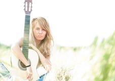 Härlig kvinna med gitarren som sitter på gräs. royaltyfri bild