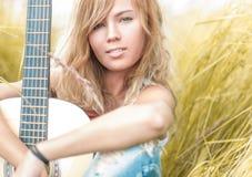 Härlig kvinna med gitarren som sitter på gräs. royaltyfria foton