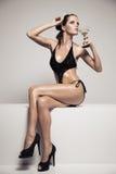 Härlig kvinna med glamoursmink i stilfull svart swimwear Drinkexponeringsglascoctail royaltyfria bilder