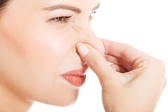 Härlig kvinna med grimasen på grund av dålig lukt. Arkivfoto