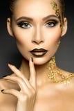 Härlig kvinna med guld- makeup Fotografering för Bildbyråer