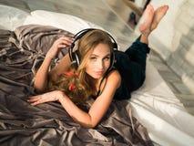 Härlig kvinna med hörlurar i säng som lyssnar till musik Royaltyfria Bilder