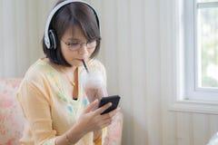 Härlig kvinna med hörlurar och smartphonen som kopplar av på royaltyfri fotografi