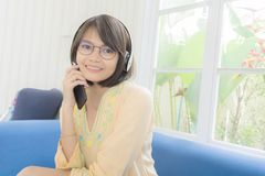 Härlig kvinna med hörlurar och smartphonen som kopplar av på arkivbild