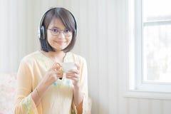 Härlig kvinna med hörlurar och smartphonen som kopplar av på arkivfoto