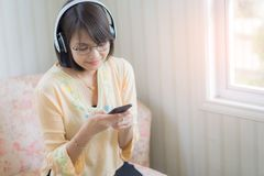 Härlig kvinna med hörlurar och smartphonen som kopplar av på fotografering för bildbyråer