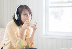 Härlig kvinna med hörlurar och smartphonen som kopplar av på royaltyfri bild