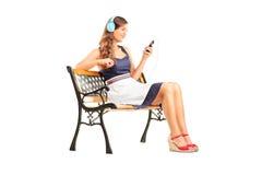 Härlig kvinna med hörlurar som sitter på bänk Arkivbilder